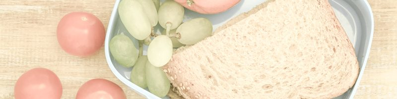 Healthy school lunch box containing brown sandwich with cheese, cherry tomatoes, mandarine and grapes